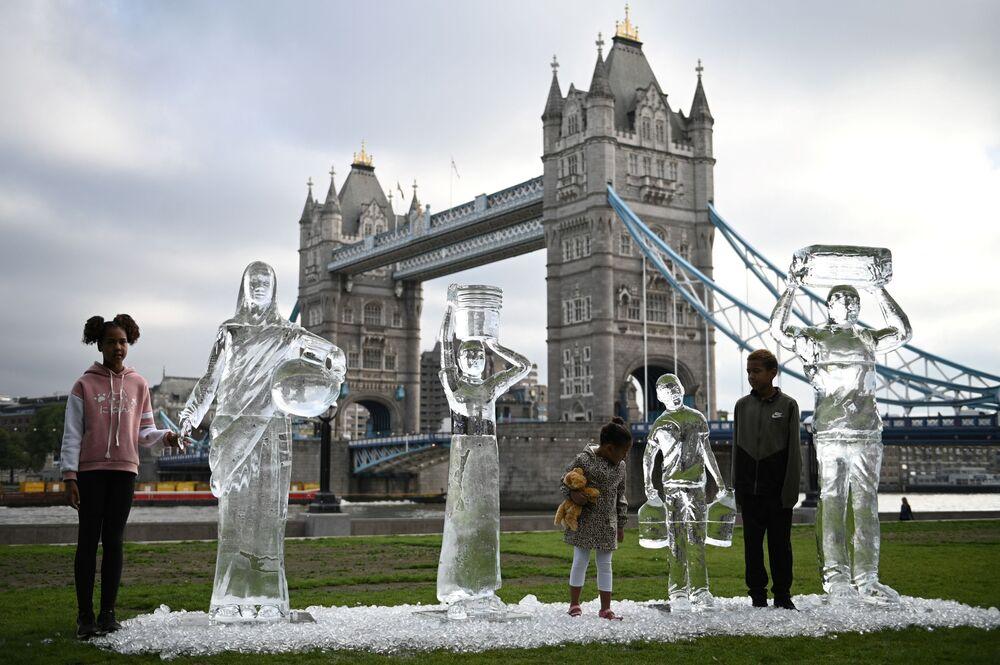 Crianças pousando perto de estátuas de gelo em Londres, no Reino Undio, refletindo a fragilidade da água ante as alterações climáticas, em 15 de setembro de 2021