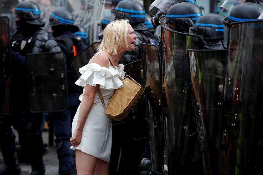 Mulher grita para policiais durante protestos contra restrições da COVID-19 em Paris, França, em 11 de setembro de 2021