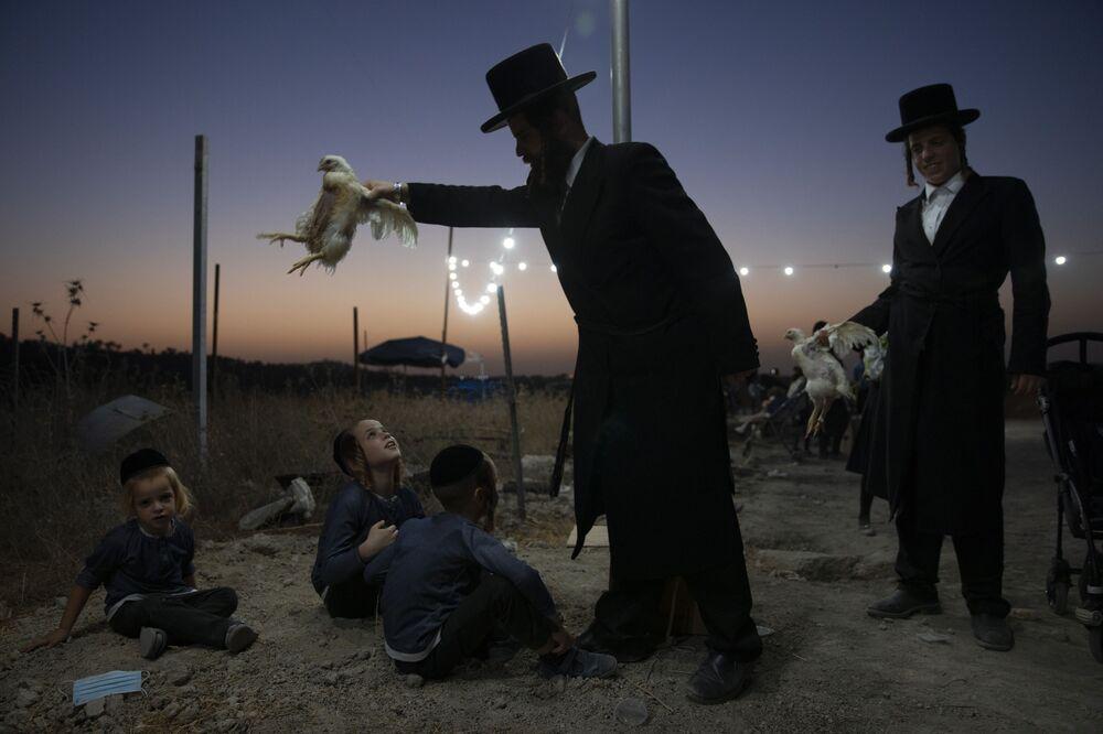 Homem judeu ultra-ortodoxo estende galinha sobre crianças como parte de ritual Kaparot em Beit Shemesh, em Israel, em 13 de setembro de 2021