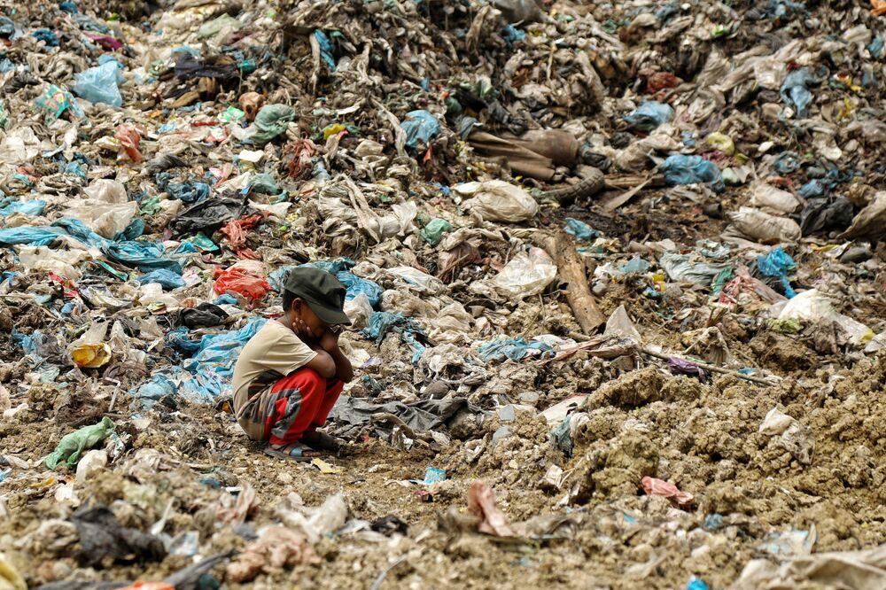 Criança procura por objetos que possam vir a ser vendidos em lixeira de  Alue Liem, em Lhokseumawe, na Indonésia, em 15 de setembro de 2021