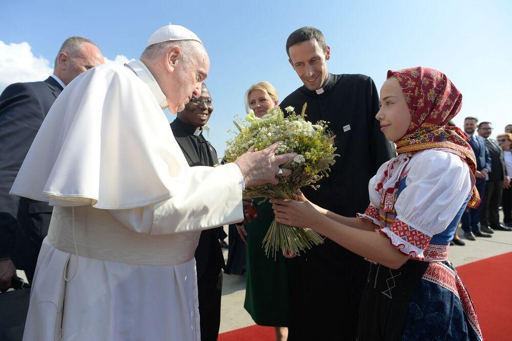 Papa Francisco é recebido por criança eslovaca usando roupas tradicionais em Bratislava, em 12 de setembro de 2021