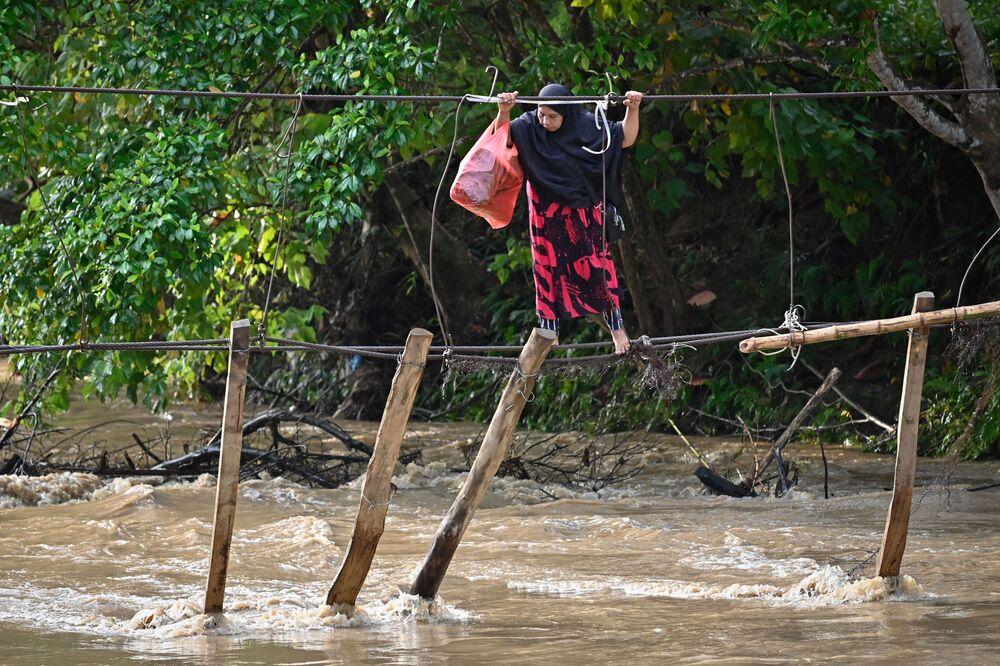 Nas fotos da semana: Mulher atravessa restos de uma ponte na localidade de Malela, no sul de Sulawesi, na Indonésia, em 13 de setembro de 2021