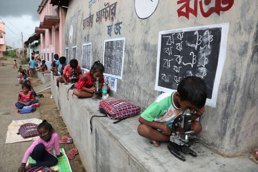 Crianças sem acesso à Internet utilizam miscroscópios em aula ao ar livre na aldeia de Joba Attpara, no estado indiano de Bengala ocidental, em 13 de setembro de 2021