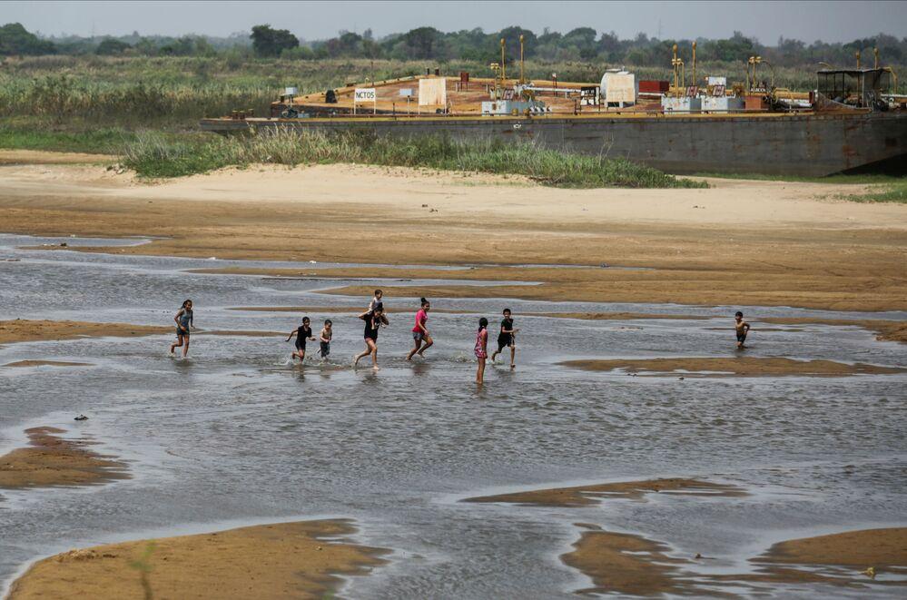 Crianças brincam nas margens do rio Paraguai, em Lambare, na República do Paraguai, uma vez que a falta de chuva no Brasil, onde o rio nasce, fez baixar o nível da água, em 13 de setembro de 2021
