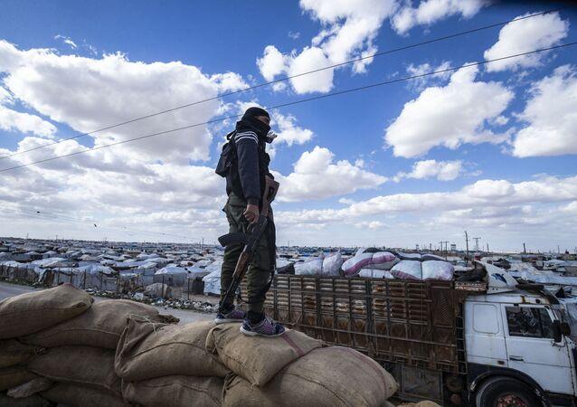 Membro das forças de segurança interna curdas observa o acampamento curdo Al-Hol, que detém familiares de combatentes do Daesh (organização terrorista, proibida na Rússia e em vários outros países) suspeitos, na província de Al-Hasakah, nordeste da Síria, 18 de março de 2021