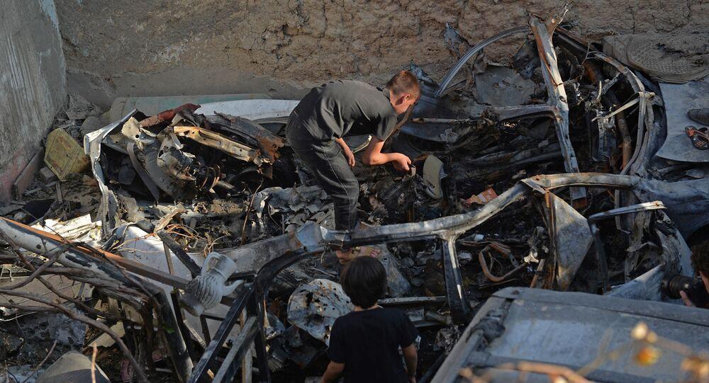 Parente de Zemari Ahmadi inspeciona os destroços do veículo atingido por ataque de drone dos EUA em Cabul, em 18 de setembro de 2021