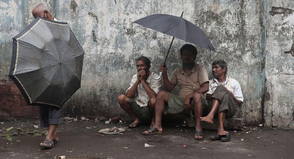 Trabalhadores assalariados diários esperam para ser empregados para o dia em uma rua em Mumbai, Índia, 11 de junho de 2021