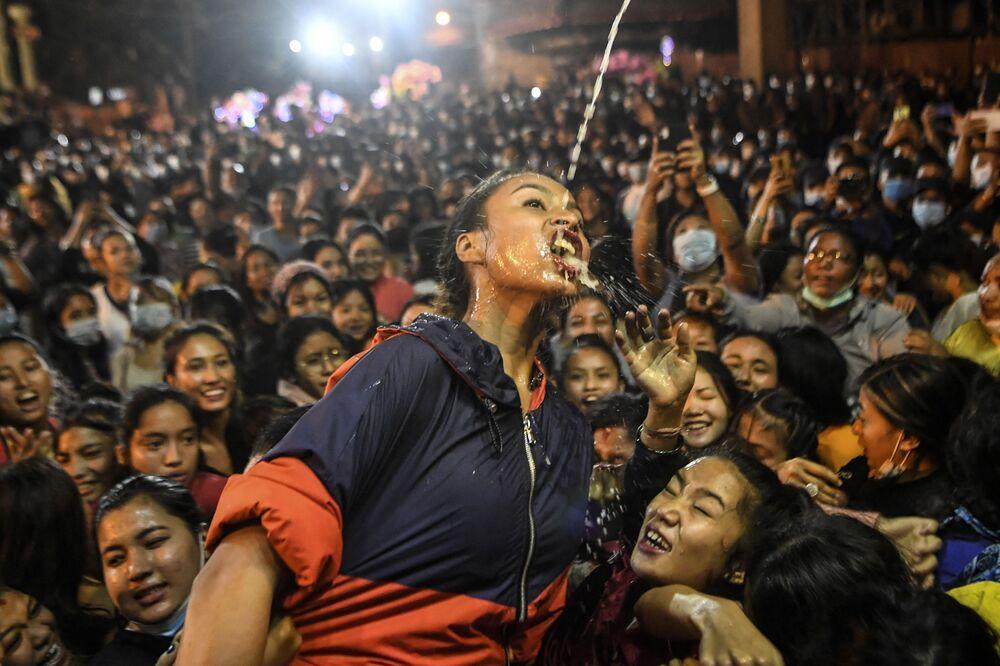 Mulher bebendo vinho que jorra da estátua de Shwet Bhairav (deus protetor) durante o festival hindu Indra Jatra em Kathmandu, no Nepal, em 21 de setembro de 2021