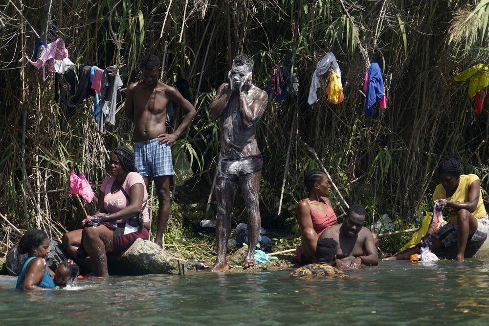 Refugiados haitianos se lavando nas margens do rio Grande durante travessia do México para os EUA, em 18 de setembro de 2021