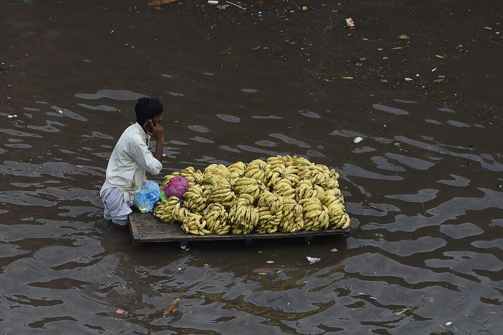Vendedor de frutas empurra sua mercadoria através de rua submersa por enchente em Lahore, no Paquistão, em 21 de setembro de 2021