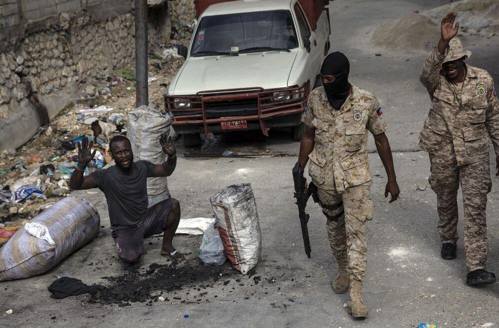 Homem levanta seus braços em sinal de inocência enquanto forças policiais patrulham as ruas de Porto Príncipe, no Haiti, em 22 de setembro de 2021