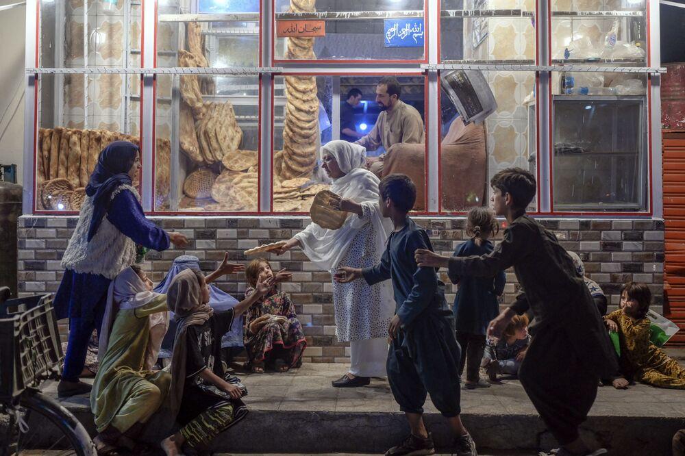 Mulher oferece pão a jovens pobres em Cabul, no Afeganistão, em 19 de setembro de 2021