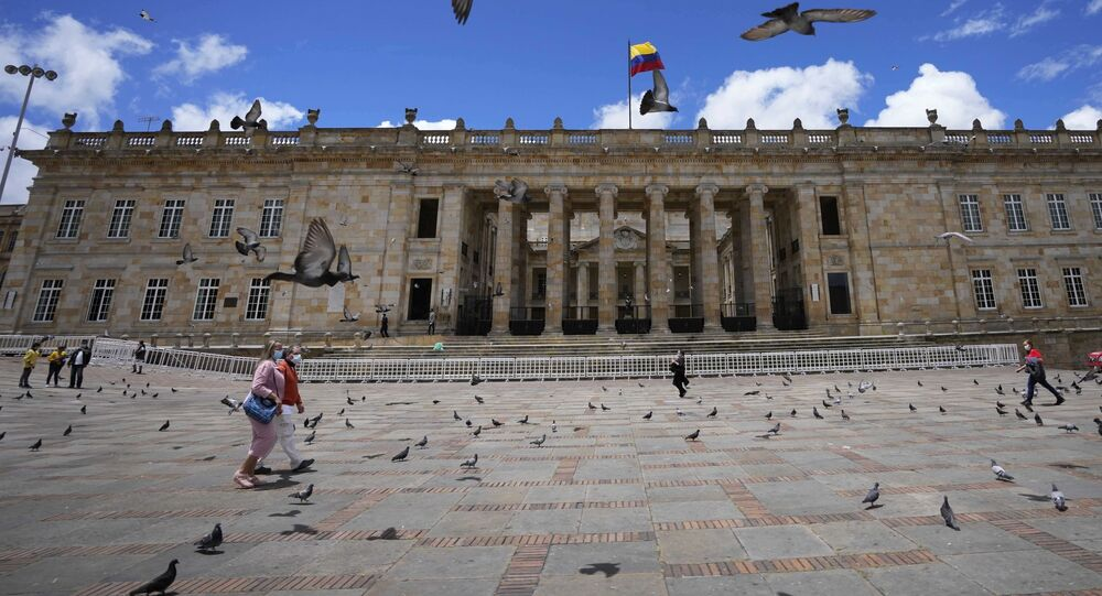 Pedestres caminham pela Praça Bolívar junto do Capitólio Nacional em Bogotá, Colômbia, 22 de setembro de 2021