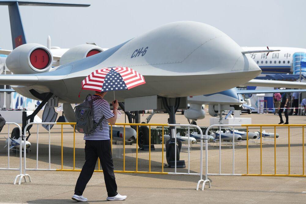 Homem com guarda-chuva com as cores da bandeira dos EUA passa por um drone CH-6, 28 de setembro de 2021