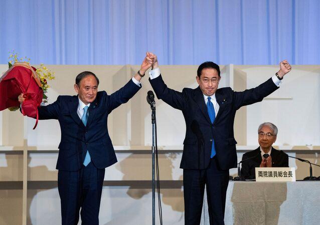 Ex-chanceler do Japão, Fumio Kishida, celebra vitória ao lado do premiê demissionário Yoshihide Suga, na eleição do novo líder do partido no poder do Japão, 29 de setembro de 2021