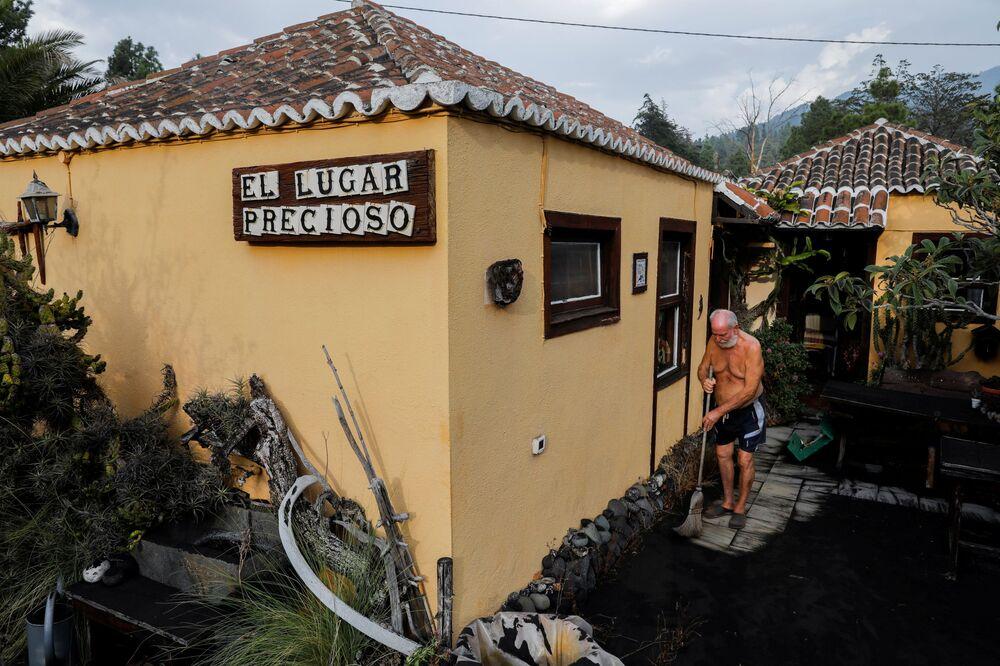 Residente de 75 anos, que foi evacuado há uma semana, limpa a entrada de sua casa coberta por cinzas após a erupção vulcânica em La Palma, nas ilhas Canárias, Espanha, 27 de setembro de 2021