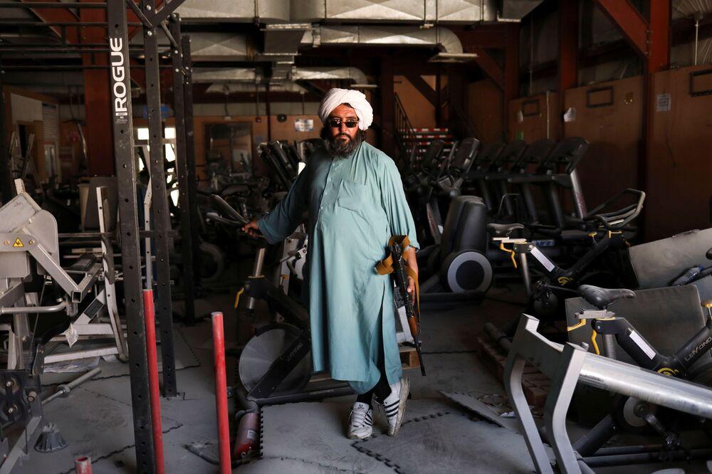 Soldado talibã armado e ex-prisioneiro perto de aparelhos de ginástica na base aérea de Bagram, na província de Parwan, Afeganistão, 23 de setembro de 2021