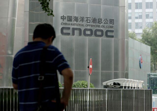 Homem do lado de fora do prédio da sede da petrolífera chinesa CNOOC, em Pequim. Foto de arquivo