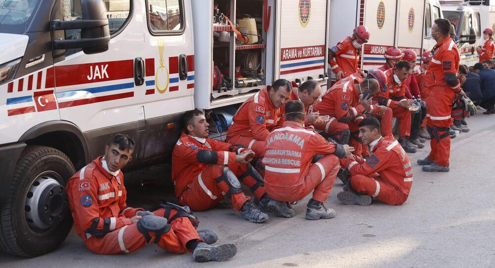 Membros dos serviços de resgate fazem pausa na busca de sobreviventes nos escombros de um prédio desabado em Izmir na Turquia