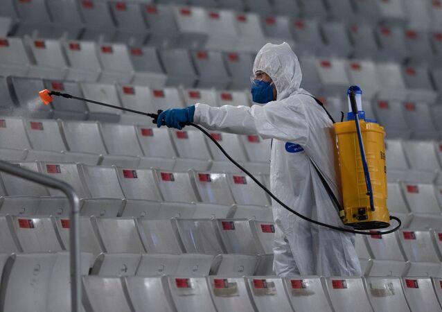 Funcionário desinfectando arquibancadas na Arena da Baixada, em Curitiba, Brasil, 30 de setembro de 2021