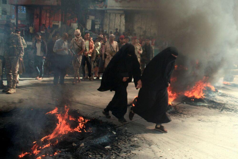 Mulheres correm no fundo de pneus em chamas durante protestos contra a deterioração da situação econômica e a desvalorização da moeda no Iêmen, 27 de setembro de 2021