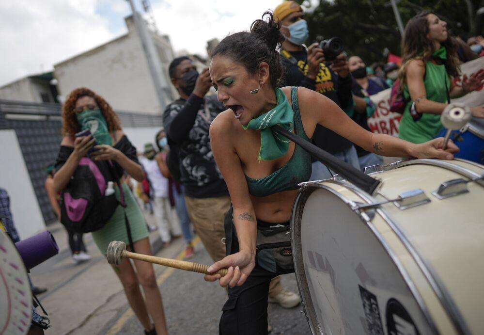Mulher toca tambor durante o Dia Global de Ação pelo Acesso ao Aborto Legal, Seguro e Gratuito, em uma praça em Caracas, Venezuela, 28 de setembro de 2021