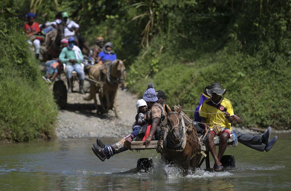 Migrantes haitianos cruzam um rio a caminho da fronteira com o Panamá em Acandí, Colômbia, 25 de setembro de 2021