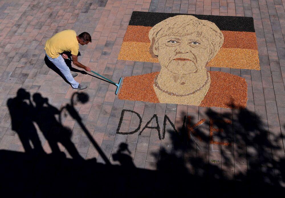 Artista de Kosovo Alkent Pozhegu termina o retrato da chanceler alemã Angela Merkel, feito de grãos e sementes, na cidade de Gjakova, 26 de setembro de 2021