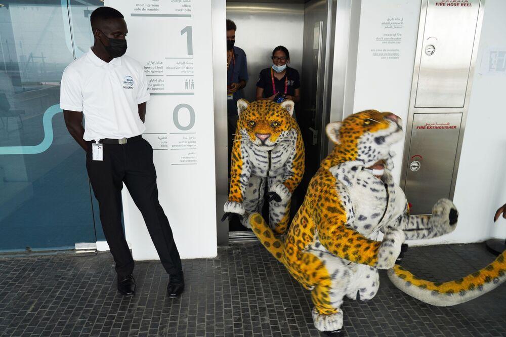 Artistas vestidos de onça saem de elevador no pavilhão do Brasil na Expo 2020 em Dubai, Emirados Árabes Unidos, 1º de outubro de 2021