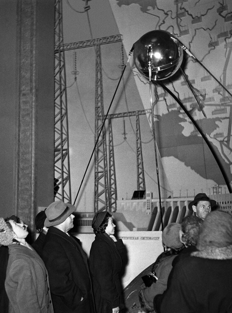 Visitantes olham para uma cópia do primeiro satélite artificial da Terra lançado em 4 de outubro de 1957, pavilhão do Centro de Exibição das Realizações da Economia Nacional, Moscou