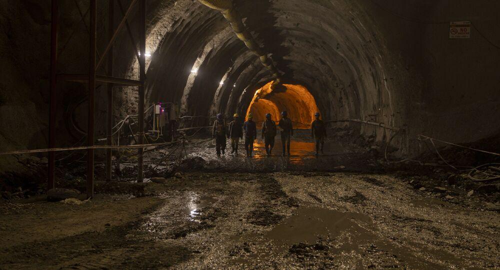 Trabalhadores caminhando dentro do túnel Nilgrar na área de Baltal, situada no nordeste de Srinagar, em Caxemira, em 28 de setembro de 2021