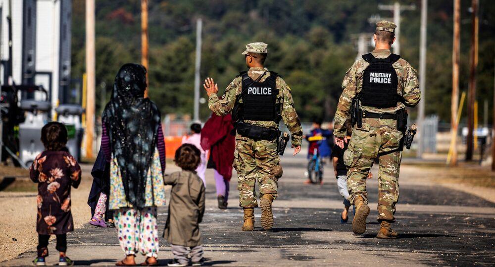 Soldados da Polícia Militar dos EUA e refugiados afegãos na base militar norte-americana de Fort McCoy, Wisconsin, EUA, 30 de setembro de 2021