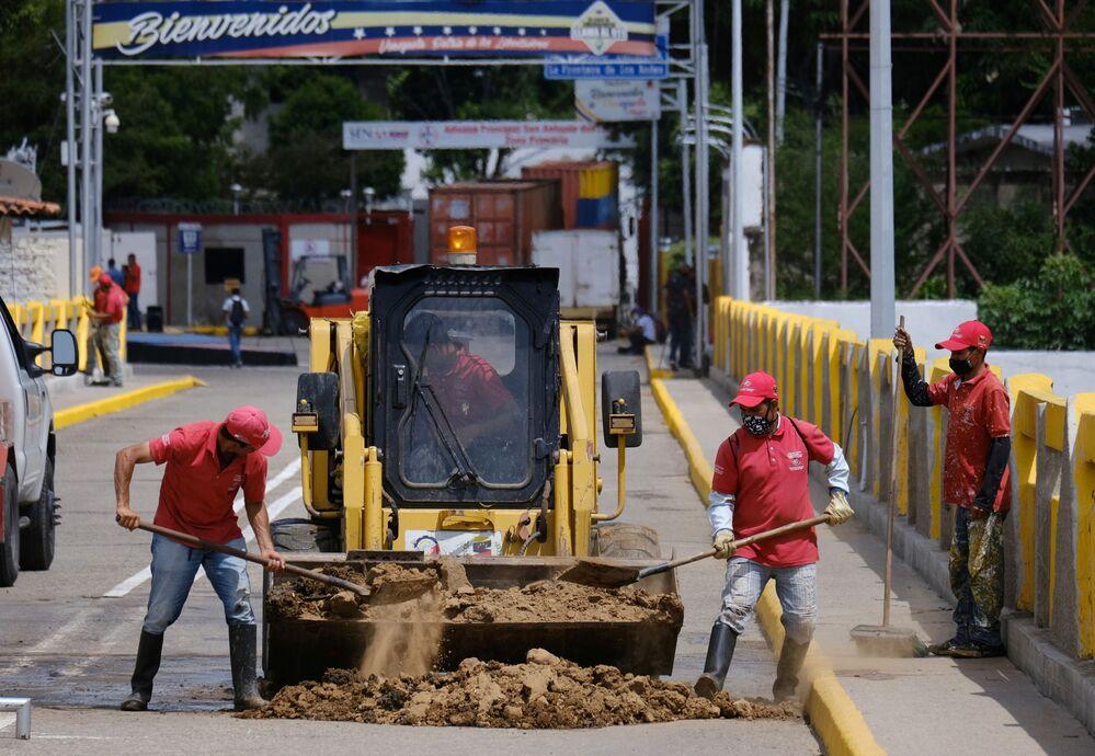 Operários tapam um buraco onde havia um contêiner bloqueando a passagem na Ponte Internacional Simón Bolívar, 4 de outubro de 2021