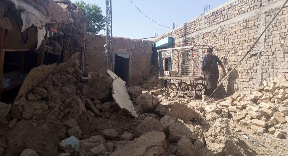 Homem remove seu carrinho de mão dos escombros de uma casa danificada pelo terremoto em Harnai, Paquistão, em 7 de outubro de 2021