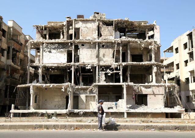 Homem passa por prédio danificado em Homs, Síria, 3 de outubro de 2021