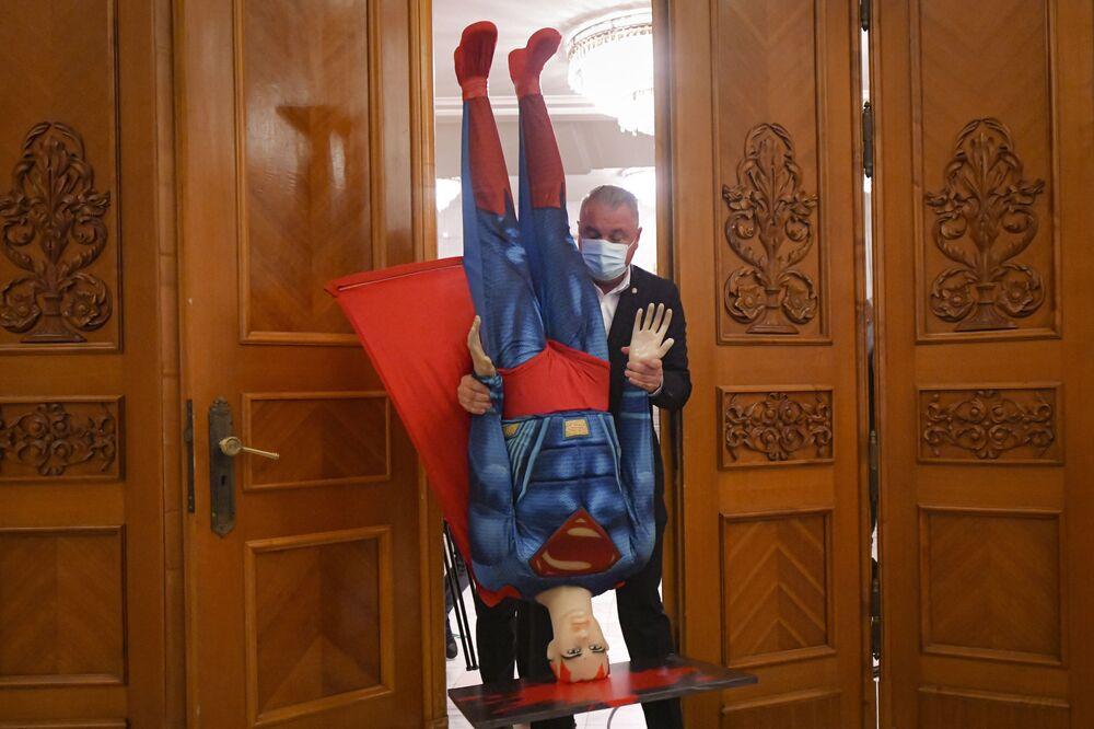 Homem carregando uma figura do Super Homem para fora do parlamento romeno, em Bucareste, na Romênia, em 5 de outubro de 2021
