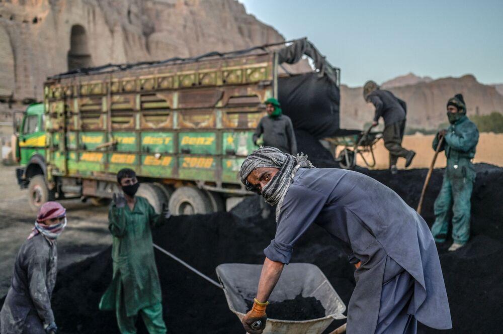 Trabalhadores de mina de carvão enchendo caminhão na província de Bamiyan, no Afeganistão, em 3 de outubro de 2021