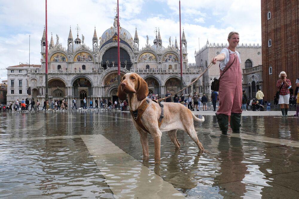 Jovem mulher posa com seu cachorro para fotografia na Praça de São Marcos inundada, em Veneza, na Itália, em 5 de outubro de 2021