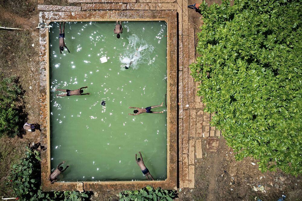 Fotografia aérea mostra garotos saltando para a água em Bangalore, na Índia, em 4 de outubro de 2021