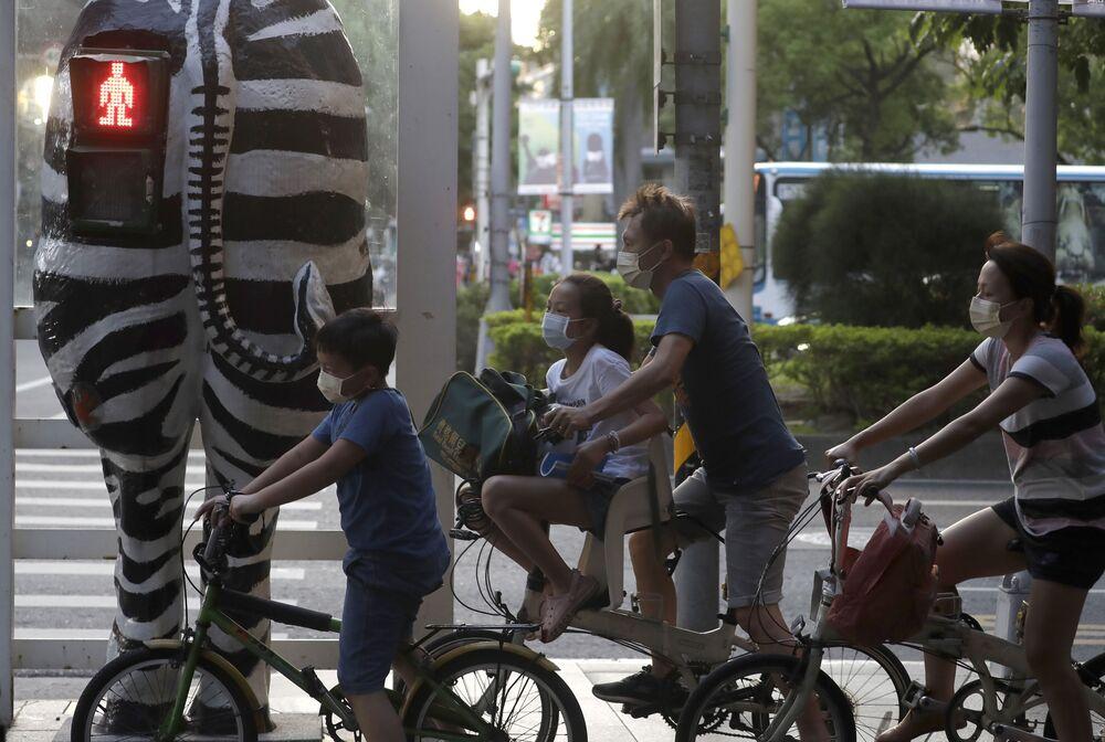 Família espera que semáforo passe para verde em Taipé, Taiwan, em 6 de outubro de 2021
