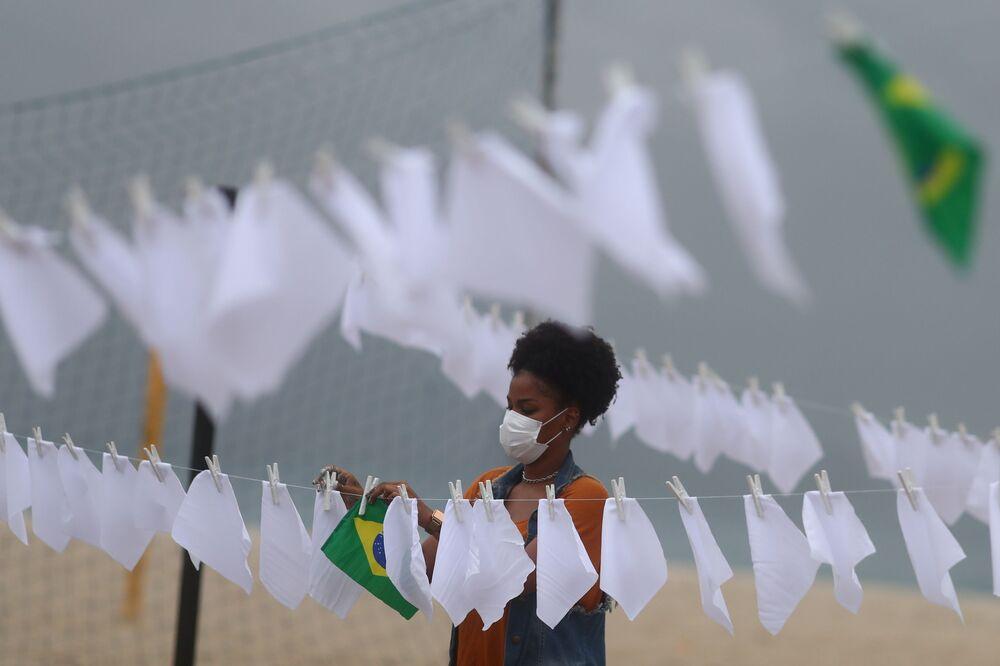 Ativista da organização sem fins lucrativos Rio de Paz, estende lenços brancos junto a bandeira do Brasil, simbolizando as mais de 600 mil mortes em resultado da COVID-19 no país, no Rio de Janeiro, no Brasil, em 8 de outubro de 2021