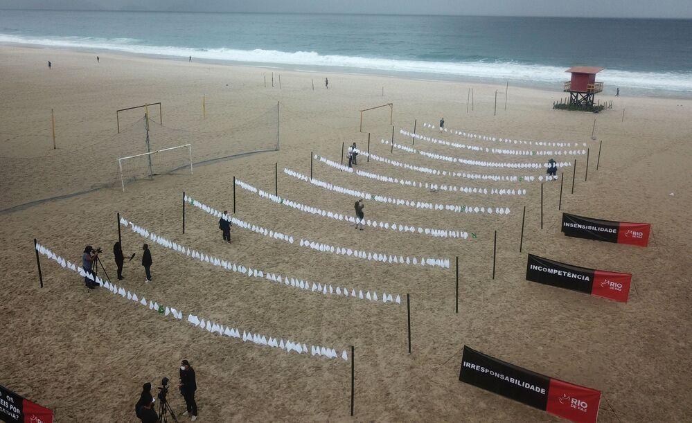 Lenços brancos são estendidos em homenagem às mais de 600 mil vítimas da COVID-19, na praia de Copacabana, no Rio de Janeiro, no Brasil, em 8 de outubro de 2021