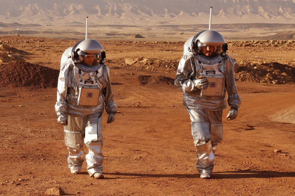 Astronautas de equipes da Europa e Israel caminham em trajes espaciais durante treinamento para missão em Marte na cratera de Ramon, no deserto de Negev, sul de Israel, em 10 de outubro de 2021