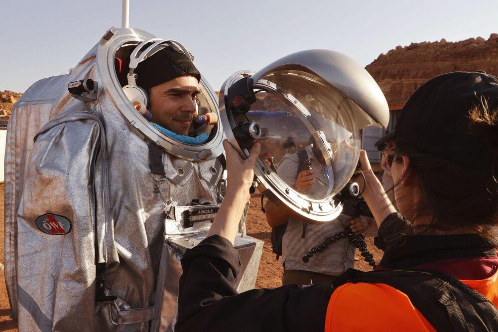 Assistentes técnicos ajudam a garantir que seu traje espacial está bem colocado antes de uma missão de treinamento, em Israel, em 10 de outubro de 2021