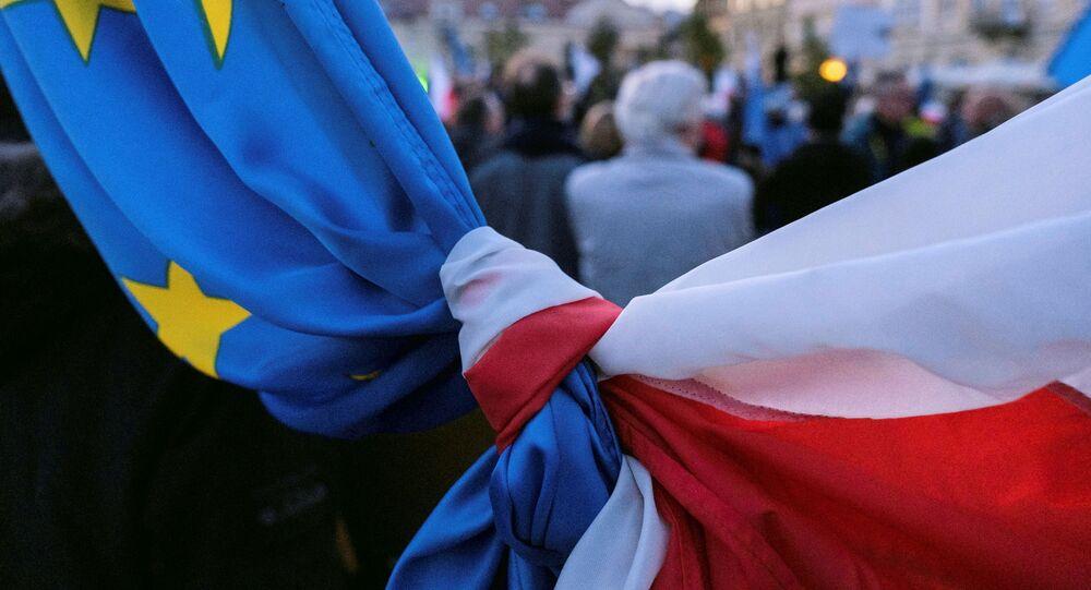 Bandeiras da Polônia e União Europeia entrelaçadas durante marcha em apoio à permanência do país no bloco europeu