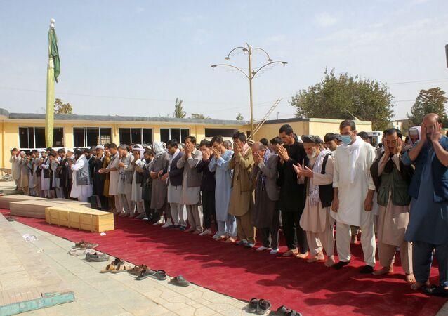 Afegãos rezam sobre os caixões de vítimas da explosão detonada por um homem-bomba no dia anterior em uma mesquita na província de Kunduz, Afeganistão, 9 de outubro de 2021