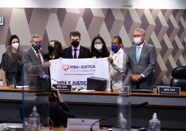 A gaúcha Rosane Brandão, que perdeu o marido para o coronavírus, entrega à CPI faixa pedindo justiça às famílias vitimadas pela pandemia, Brasília, 18 de outubro de 2021