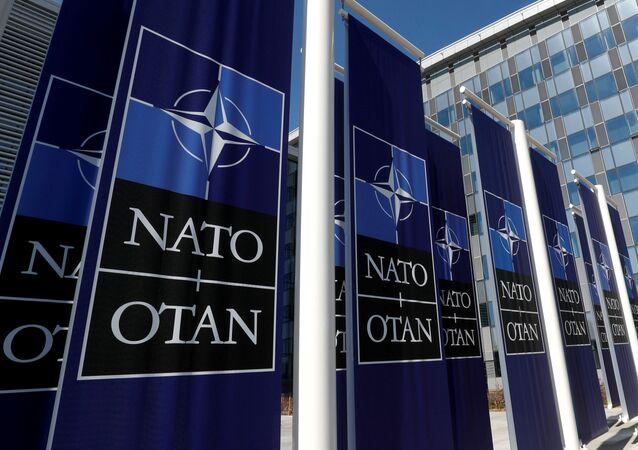 Cartazes mostrando o logo da OTAN colocados na entrada da sede da aliança, em Bruxelas, Bélgica