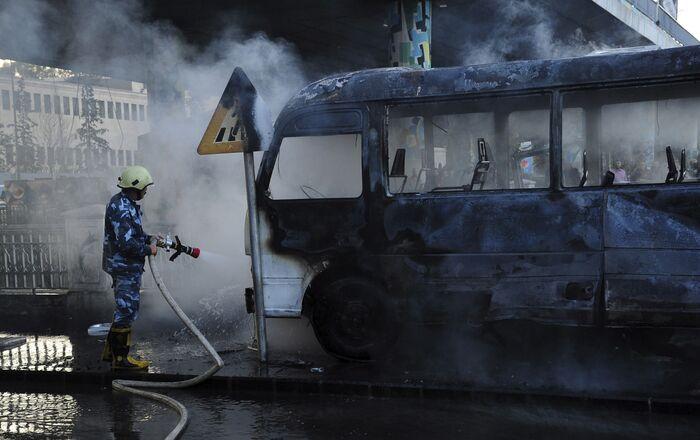 Foto divulgada pela agência de notícias SANA mostra bombeiro apagando fogo de ônibus atingido por explosão em Damasco, Síria, 20 de outubro de 2021
