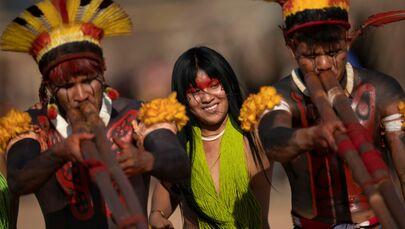 Representantes das tribos Yawalapiti, Kalapalo e Mehinako tocam flautas uruá enquanto dançam durante ritual fúnebre Kuarup para homenagear a memória do cacique Aritana no Parque Indígena do Xingu